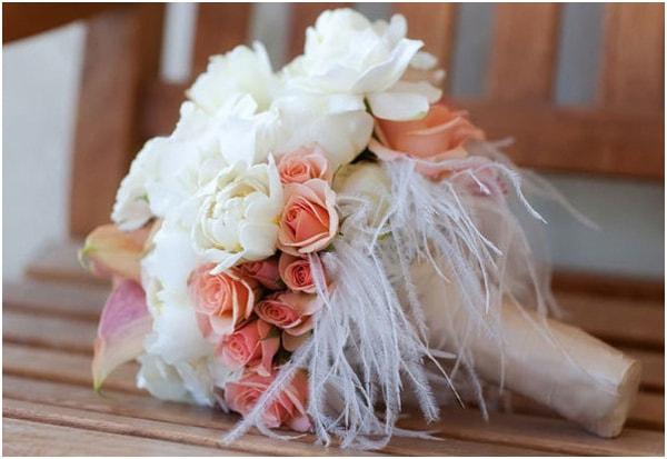 Bó hoa hồng cầm tay kết hợp với lông vũ trắng cho vẻ đẹp tinh khôi, thuần khiết