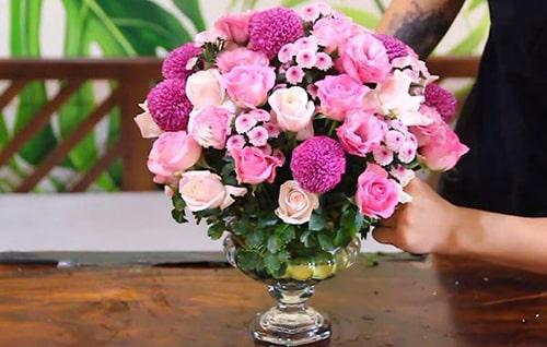 Dùng bình thủy tinh chân cao, cắm đan xen hồng phấn và hồng nhạt để bàn sang trọng tinh tế