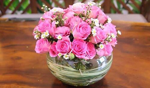 Sử dụng bình thủy tinh tròn trong suốt, ghép các cành hồng bắt chéo gốc để tạo hình vòm tròn. Lồng thêm hoa phụ để trang trí làm hoa hồng nổi bật